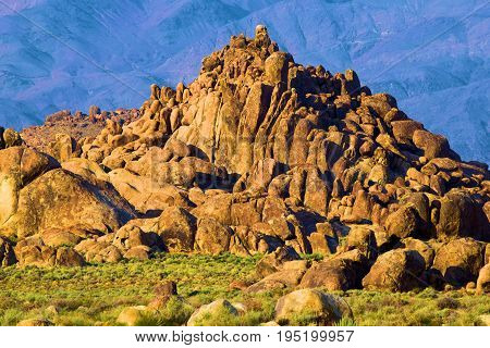 Hill of rocks surrounded by an arid desert landscape taken at the Alabama Hills in Lone Pine, CA