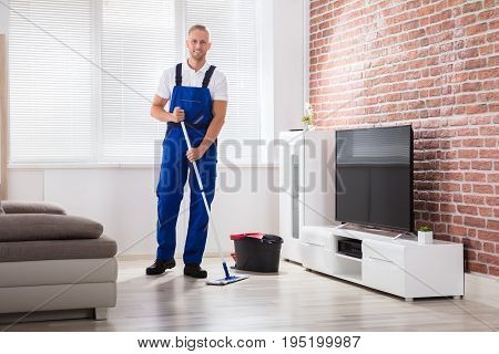 Portrait Of A Happy Male Janitor In Uniform Sweeping Floor With Broom