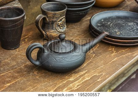 On the wooden table is ceramic hand-made pottery
