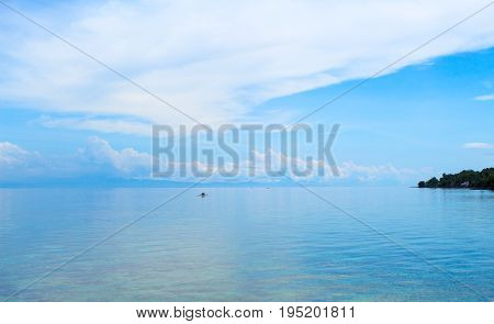 Blue seascape with fishing boat and blue sky. Relaxing sea view with still seawater. Seaside vacation day. Blue sky and water reflection. White cloud on blue sky. Tropic seashore. Holiday banner