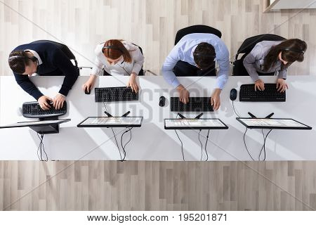 Elevated View Of Call Center Operator Team With Headset Working In Office