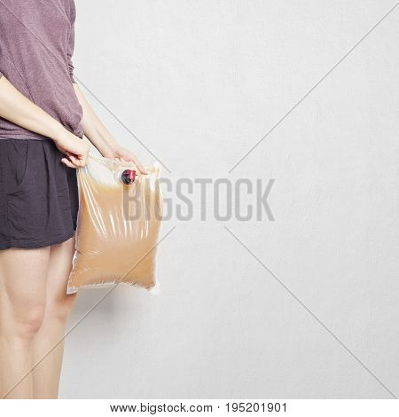 Girl holding plastic bag with tap full of apple juice, stucco wall background