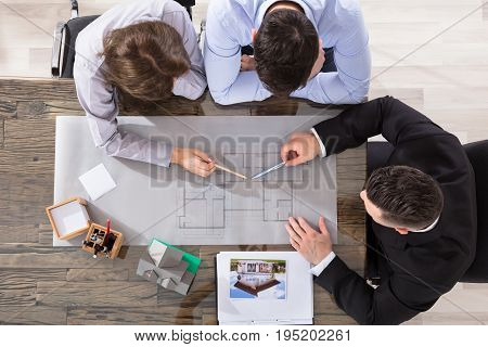 Elevated View Of Architect Working On Blueprint With Couple