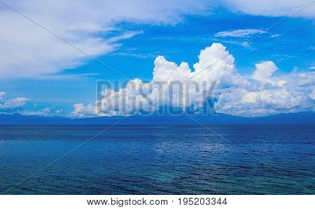Sea landscape with clouds. Turquoise blue seascape. Tropical seaside minimal photo for wedding background. Peaceful cumulus on horizon. Tropical climate or weather change. Tropical island landscape