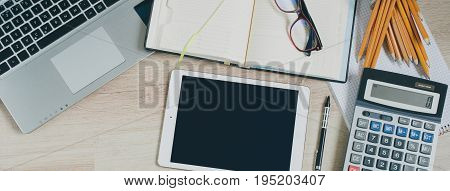 Office desk table with computer, tablet, supplies and calculator. Top view with copy space, flat lay modern banner