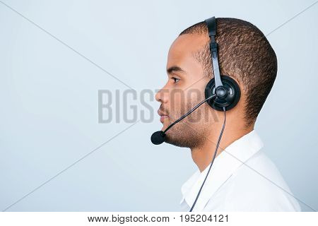 Side Profile Portrait Of A Handsome Mulatto American Guy Call Centre Operator In A Headset. He Is Is