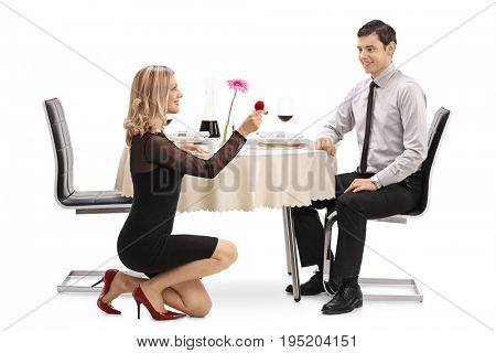 Young woman kneeling and proposing to her boyfriend at a restaurant table isolated on white background