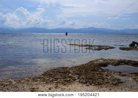 Sea landscape with fisherman silhouette. Seascape with distant island. Tropical beach view. White sand beach with blue water. Sunny day on seaside. Summer travel photo. Sand beach and still seawater
