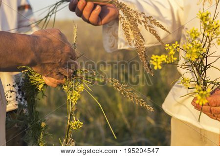 A Girl And Man In White Traditional Slavic Dress Wreathes A Wreath Of Fresh Wildflowers At Sunset. R