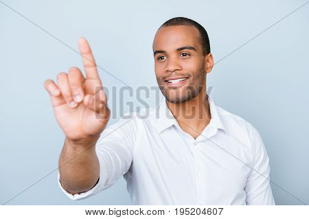 Portrait Of Smiling Successful American Mulatto Entrepreneur Touching Virtual Screen, Standing On Pu