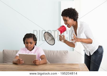 Mother Shouting At Her Daughter Holding Digital Tablet In A Megaphone At Home
