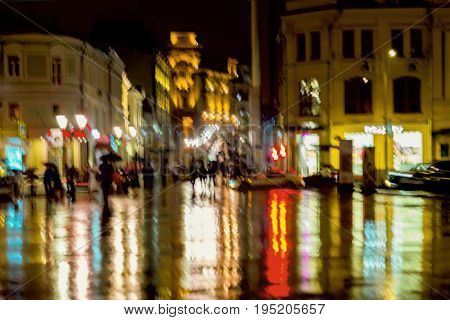 Abstract background of unrecognizable people hurrying down the city street in rainy evening. Bright lighting from shop windows and street lamps. Intentional motion blur. Concept of Lifestyle of modern city, seasons, weather