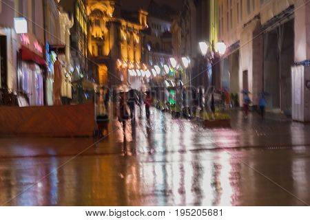 Blurred background of young people walking down the street in rainy evening, Impressionism style, colorful lighting. Intentional motion blur. Concept of seasons, weather, modern city.