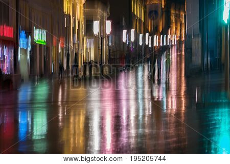 Abstract bright blurred background with unidentified people the city street in rainy night. Vivid illumination and reflection in the wet pavement from shop windows and street lamps. Concept of active healthy lifestyle, leisure