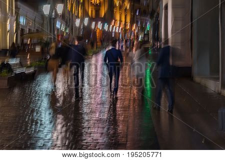 Abstract background of blurred young people walking down the street in rainy evening, Impressionism style, colorful lighting. Intentional motion blur. Concept of seasons, weather, modern city, lifestyle, leisure.