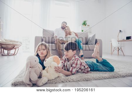 Leisure Together. Happy Family Of Four Is Enjoying At Home, Small Kids Are Playing With Toys, Parent