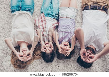 High Angle View Of Happy Family Of Four Is Joking, Lying On The Beige Cozy Carpet In A Row, At Home,