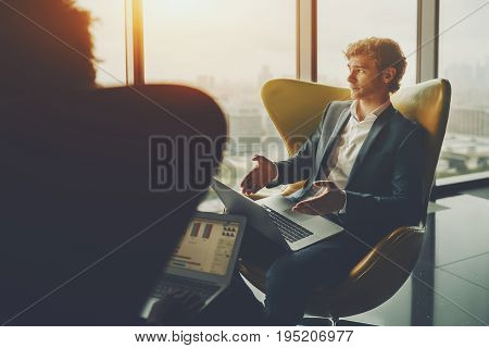 Young handsome bearded boss in formal suite is explaining to his subordinates new strategy while sitting on yellow armchair and holding laptop during work meeting with cityscape behind office window