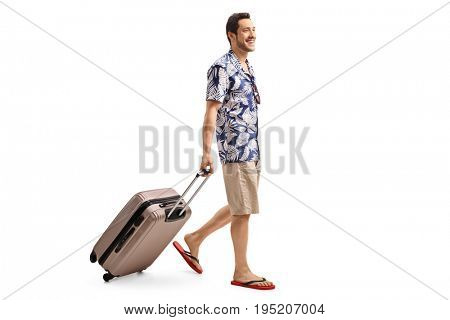 Full length profile shot of a tourist walking and pulling a suitcase isolated on white background.jpg