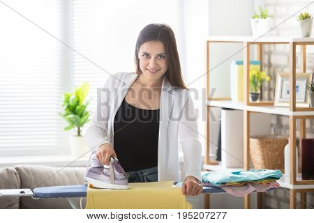 Smiling Young Woman Ironing Clothes On Ironing Board At Home