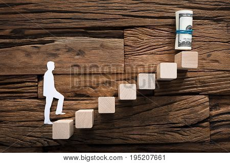 Closeup of paper businessman climbing block ladder leading towards rolled dollar bills on wood