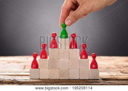 Closeup of hand placing green pawn with other red figurines on pyramid blocks