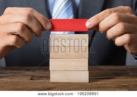 Closeup midsection of businessman placing red block on wooden tower at table