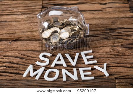 Closeup of coins in glass piggybank by save money text on wooden table