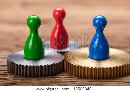 Closeup of colorful pawn figurines on cogwheels on wooden table