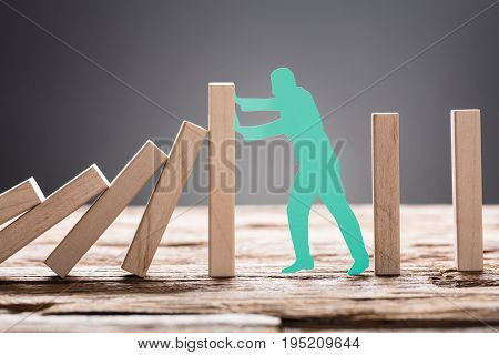 Closeup of green paper man stopping wooden domino blocks on table against gray background