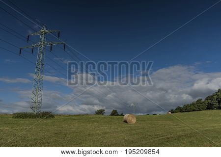 Electric poles on green meadow with hay in summer morning