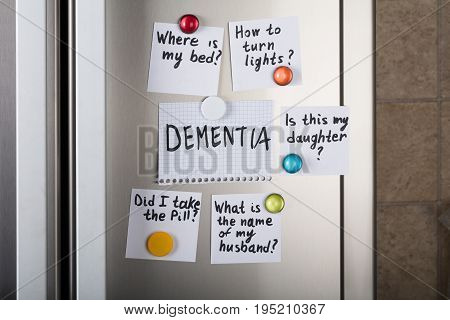 Closeup of dementia note with various reminders attached with magnetic thumbtacks on metal