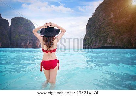 Woman in red bikini at tropical beach. Vintage tone