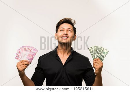 good looking young indian man holding fan of currency notes, Indian 2000 rupee and US dollar 100 paper currency notes, standing isolated over white background