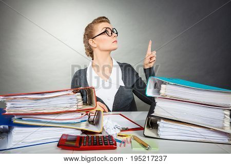Message and news concept. Serious pensive businesswoman pointing to blank copy space above documents.