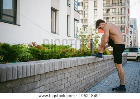 Handsome Sexy Male Bodybuilder Athlete Man With Naked Torso, Running In Morning, Outdoors. Ties Up S