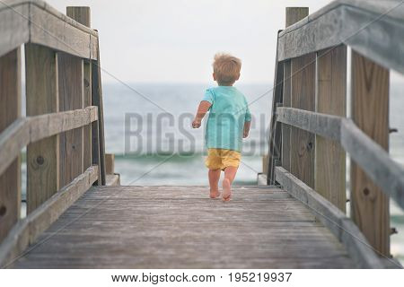 Toddler boy running on wooden deck to the beach, rear view