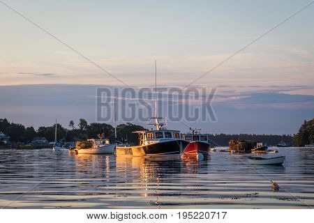 Lobster boats in the quiet and still harbor at dawn in Friendship, Maine
