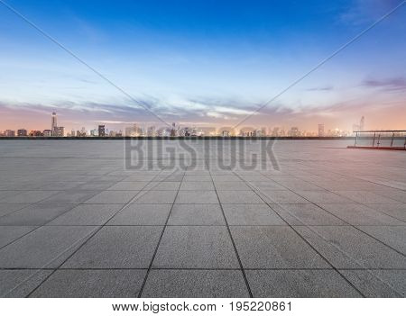 empty concrete floor with cityscape and skyline in nightfall bangkok thailand.