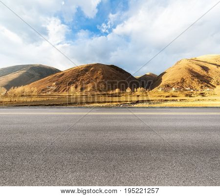 empty asphalt road with the autumn landscape. tibet words on the mountain mean :six syllable mantra about tibetan area buddhism useful expressions.