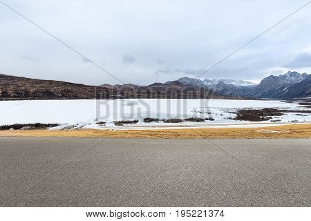 empty road with ice lake in tibetan plateau asphalt highway background
