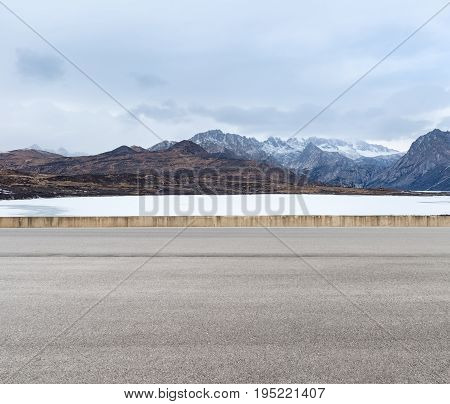 empty road with snow mountain and ice lake in tibetan plateau asphalt highway background