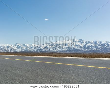 snow mountain background with empty asphalt road in golmud city China