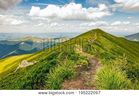 summer mountain landscape. group of tourists go by footpath uphill through the ridge to the peak