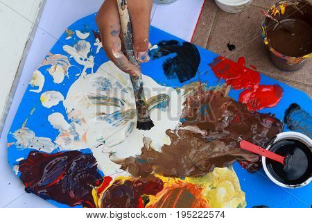 The painter uses red blue yellow black and white to mix colors to paint.