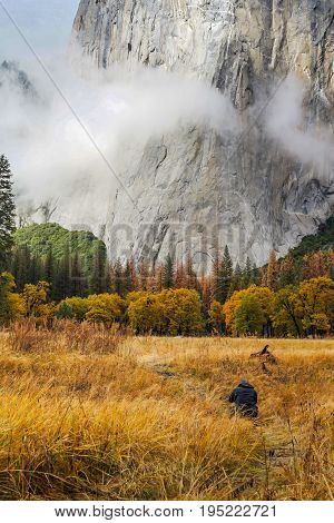A photographer/hiker is taking pictures of El Capitan at El Capitan Meadow at Yosemite National Park