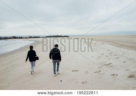 The Couple Walk On The Beach.