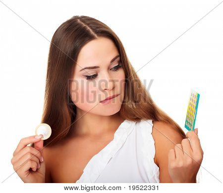 Confused pretty caucasian girl looking at condom and contraceptive pills.