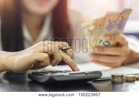 Close up right hand female using calculator and left hand hold with Euro banknotes. Calculation at home