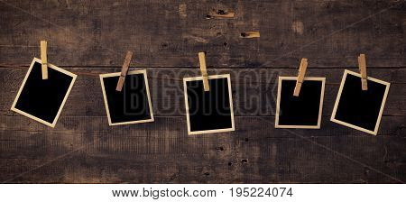 Five old photo frames on a rustic wooden wall